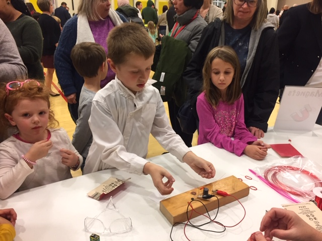 Student at table with wooden block and electrodes