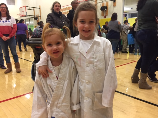 Two girls in lab coats smiling