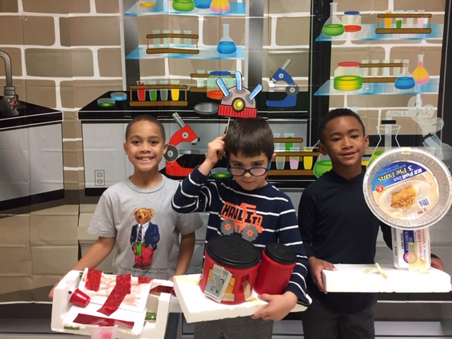 Three students displaying their creations